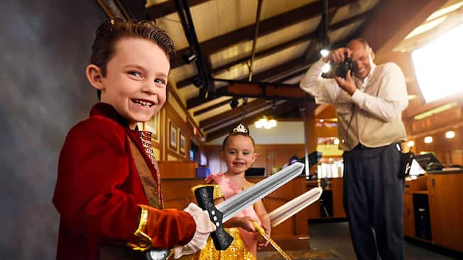 Un niño vestido de príncipe juega cerca de una niña vestida de princesa mientras un hombre les toma una foto