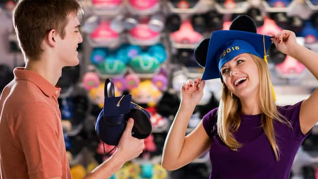 A woman tries on a graduation hat with Mickey ears that reads Class of 2016 across the front
