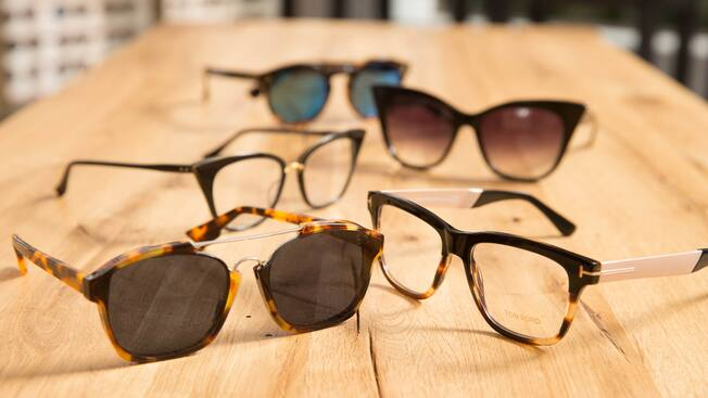 Five pairs of eyeglasses rest upon a wooden counter inside Edward Beiner Purveyor of Fine Eyewear