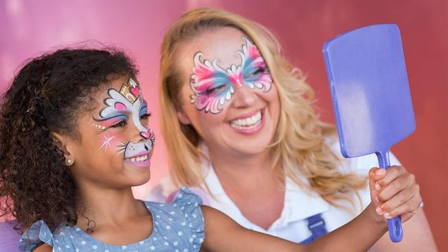 Une jeune fille tient un miroir devant son visage pour inspecter son maquillage et la peinture sur visage réalisés au kiosque Enjoy Your Face à Disney Springs alors que l'artiste la regarde
