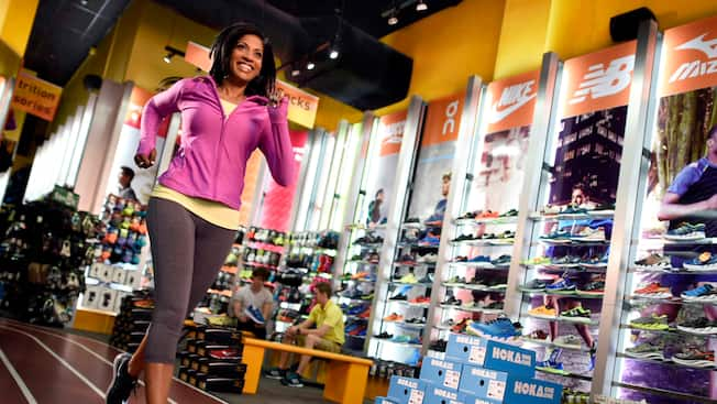 A woman tests out a pair of sneakers inside Fit 2 Run