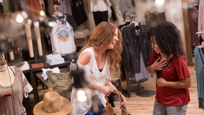 Two female friends laugh and smile as they shop inside Free People
