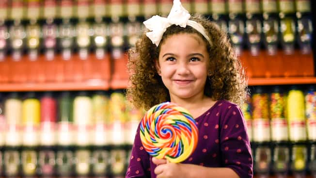 A smiling little girl holds a large lollipop inside Goofy's Candy Company