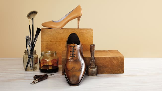 A Johnston and Murphy women's high heel shoe and men's oxford shoe on display among shoemaking tools