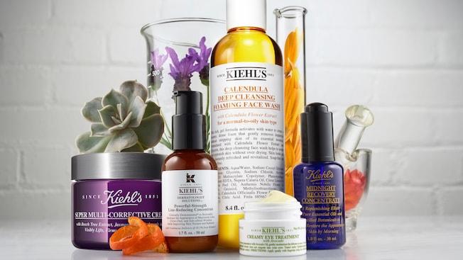 Variedad de productos para el cuidado de la piel de Kiehl exhibidos con abundantes arreglos florales dentro de vasos de precipitado de vidrio