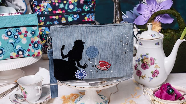 A Kipling denim wristlet pouch featuring a silhouette of Alice in Wonderland and an embroidery flower and tea cup on display among a tea serving set