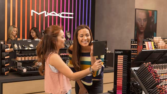 A young woman holds up a mirror for her female friend who is trying on makeup at MAC Cosmetics