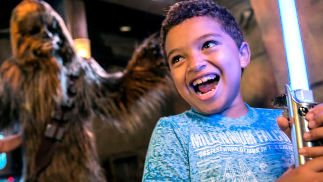 A young male Guest smiling while he holds a replica of a lightsaber inside Star Wars™ Trading Post