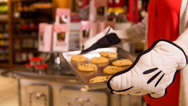 Llevan galletas con chips de chocolate recién horneadas en una bandeja de galletas, con guantes de cocina de Mickey