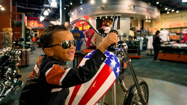 A young boy wearing sunglasses sits on motorcycle at the Orlando Harley Davidson store