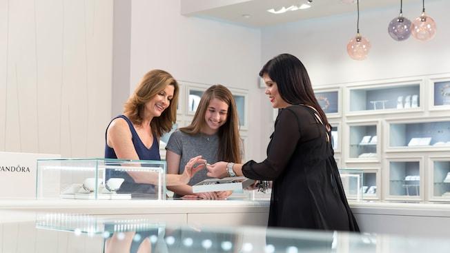 Atrás de um balcão, vendedora da Pandora mostra uma joia para uma mãe e sua filha