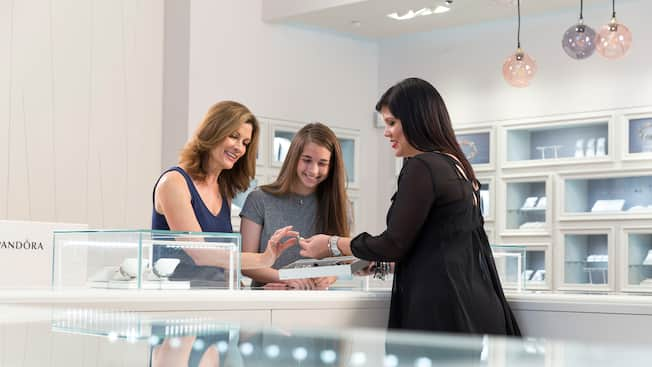 A female Pandora sales representative shows a mother and daughter a piece of jewelry from behind a display counter