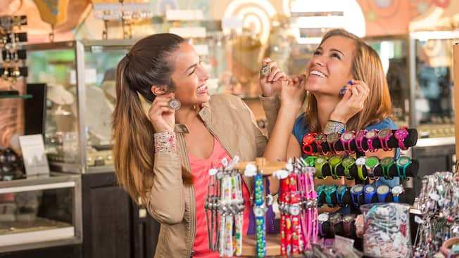 2 young women in a jewelry shop smile as they try on different pairs of earrings