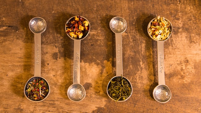 Four double ended measuring spoons laid side by side each containing a different loose leaf tea in the larger end