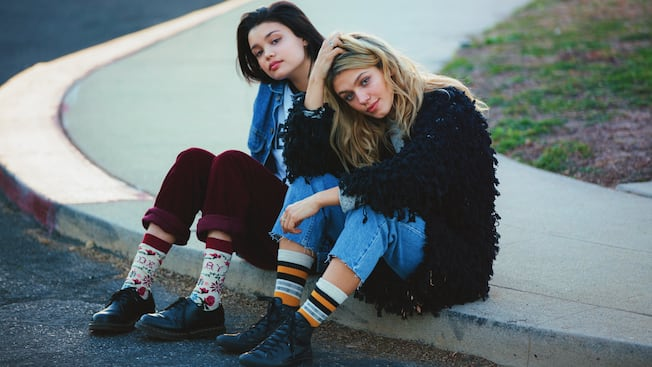 Two young females sit on a curb wearing stylish outfits with vibrant Stance socks