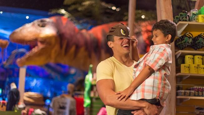 Un niño coloca una gorra de dinosaurio en la cabeza de su padre