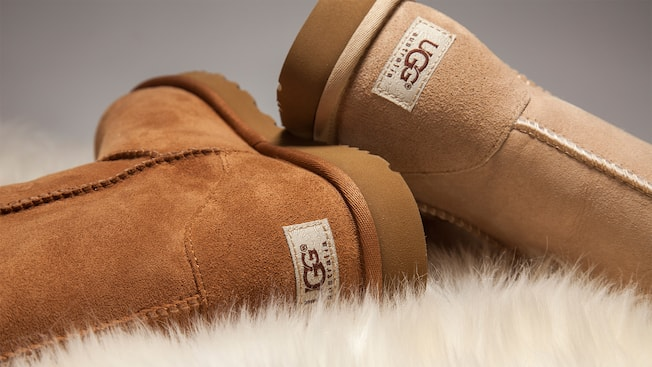 Two UGG boots rest upon a patch of sheepskin