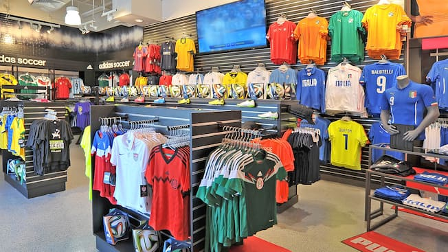 Soccer jerseys hanging on display islands and on walls inside an apparel store