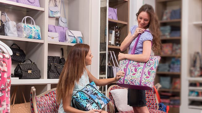 A young woman sits in a chair and admires the Vera Bradley tote her friend is carrying on her shoulder