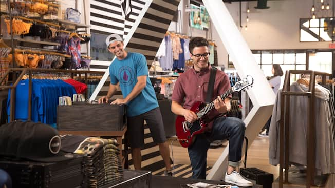 A young man plays a display guitar while his male friend looks on with amusement inside Volcom