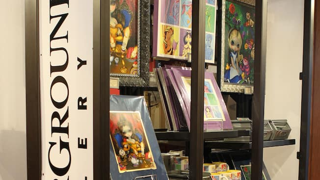 A large bookcase holds framed character art and other products at the Wonderground Gallery