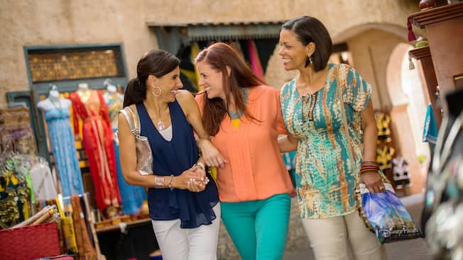 A trio of female Guests laughs with each other while walking through the Morocco Pavilion at Epcot