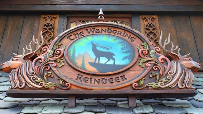 A wood carved sign on a shingle roof reveals a reindeer silhouette and the engraved words The Wandering Reindeer