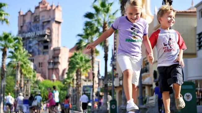 Dos hermanos saltan contentos por Sunset Boulevard vestidos con sus remeras de Mickey y Minnie Mouse.