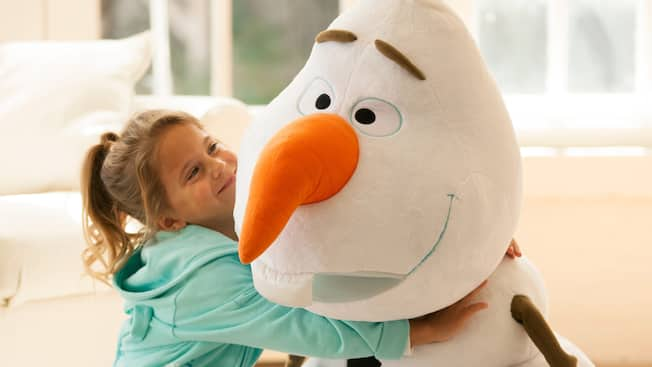 A young girl hugs a giant, plush Olaf toy