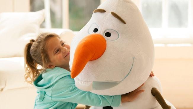 Uma menina abraça um boneco de pelúcia gigante do Olaf