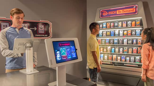 A young man operates a touch screen while a teen boy and girl look at a display offering a selection of computer games
