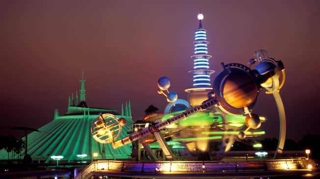 The brightly lit iconic launching pad in Tomorrowland at night