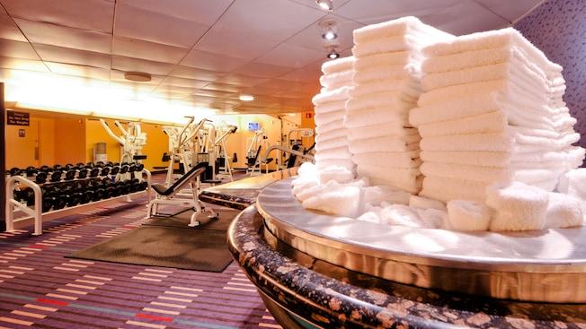 3tas de serviettes blanches pliées sur une table de marbre dans une salle d'entraînement avec des haltères  et d'autres équipements d'entraînement à l'arrière-plan
