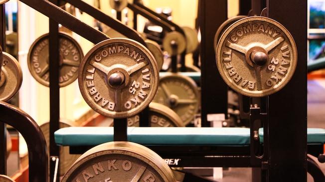 Una mujer se entrena con pesas y un hombre en una máquina elíptica en el gimnasio