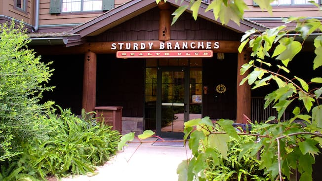 "Entrance to a brown-colored building with sign that reads ""STURDY BRANCHES HEALTH CLUB"""