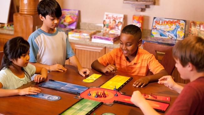 Un groupe d'enfants se rassemble autour de la table pour jouer à un jeu de société