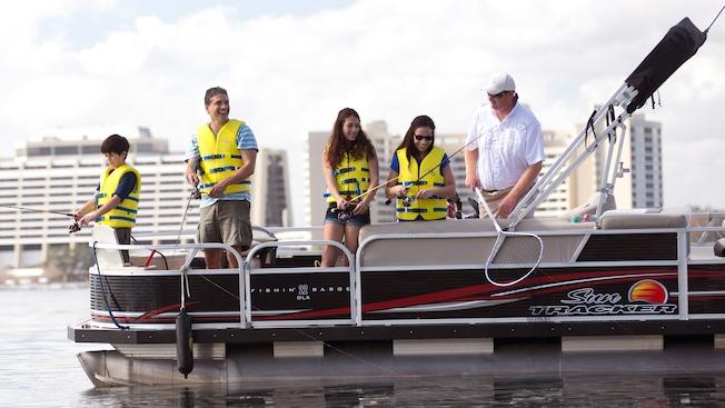 Los Huéspedes lanzan sus hilos de pesca al agua desde un pontón fuera del Disney's Contemporary Resort