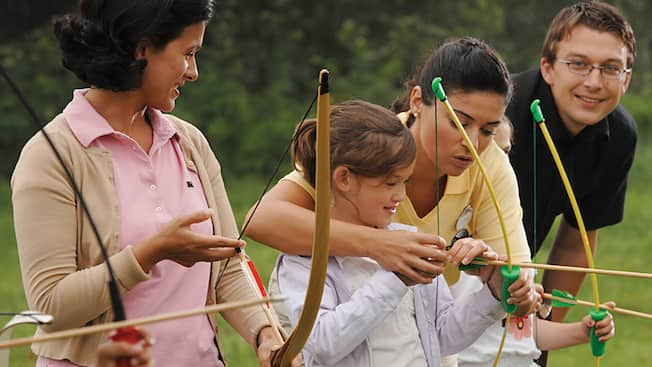 A young female Guest receiving firsthand instructions from a Cast Member during an archery lesson