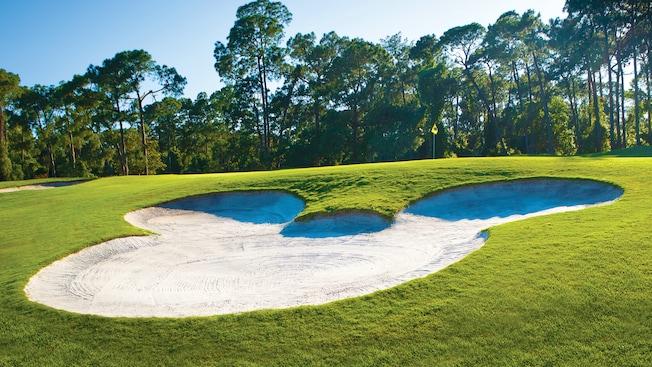 Un obstáculo de arena con la forma de Mickey cerca de un hoyo en el Disney's Magnolia Golf Course