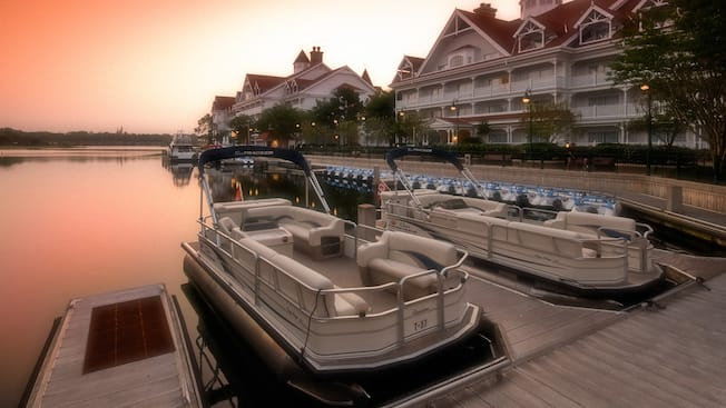 2 boats moored at a dock alongside the grounds of a Disney Resort hotel
