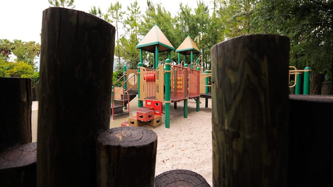 A view framed by wood logs of a children's playground