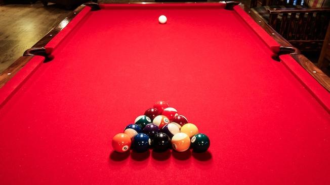 Una mesa de pool roja con las bolas agrupadas y la bola blanca en posición