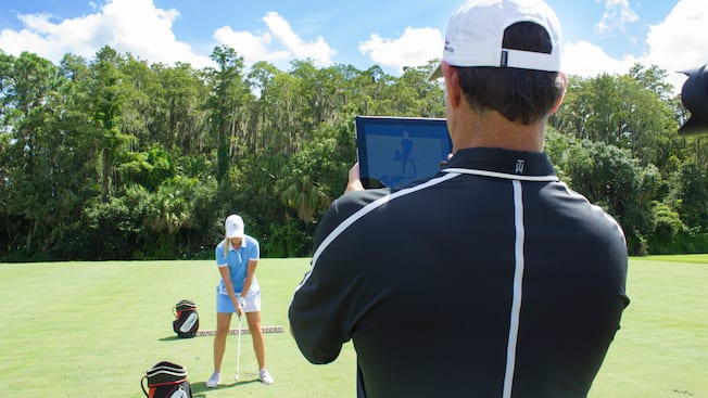 A golf instructor filming a Guest during a professional coaching session at Walt Disney World Resort