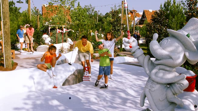Un niño balancea su palo de golf en la nieve falsa en Disney's Winter Summerland Miniature Golf Course