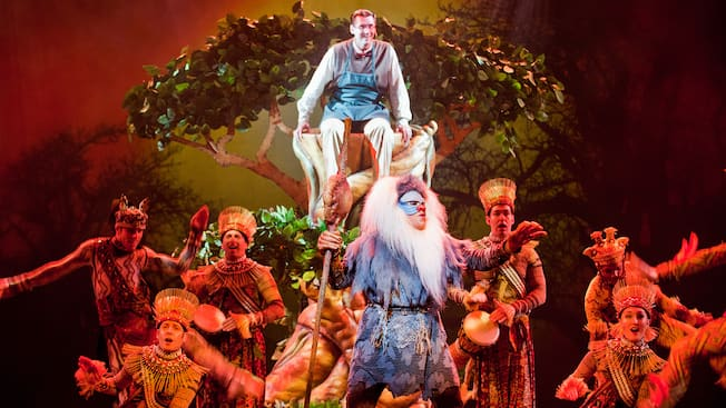 A stage play featuring a jubilant man in bow tie and apron surrounded by Lion King performers