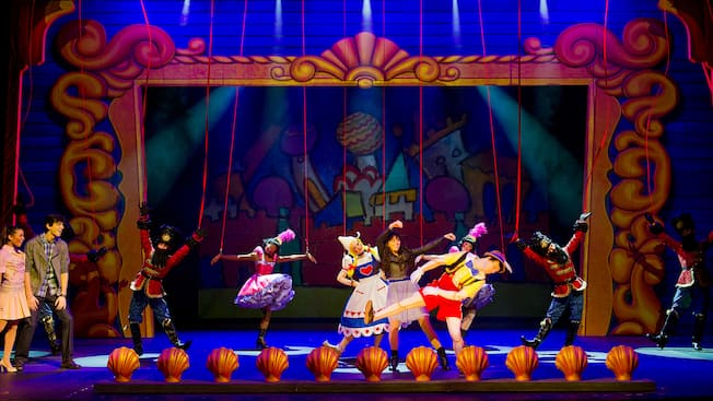 Two young people marveling at a girl, Pinocchio and a number of dancers dressed as puppets on stage