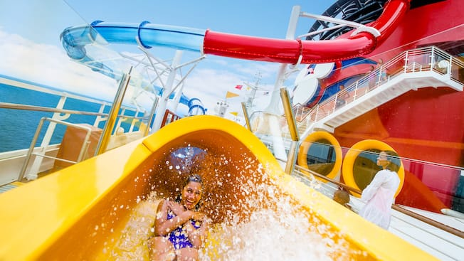 A smiling young woman watersliding with arms across her chest and feet first into the Splash Zone