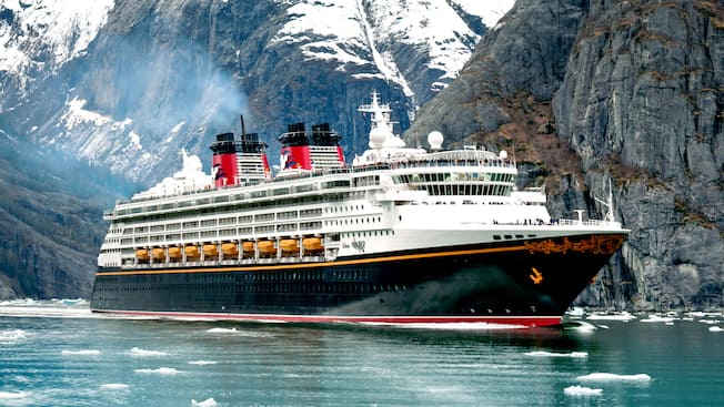 The Disney Wonder ocean liner sailing through water and ice next to a glacier mountain