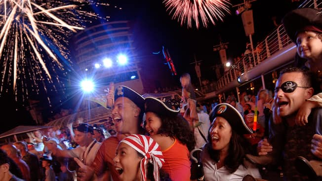An audience dressed as Pirates of the Caribbean characters marvel at the fireworks going off overhead