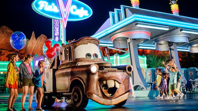 Tow Mater greets Guests at night outside the neon-lit Flo's V8 Café in Cars Land